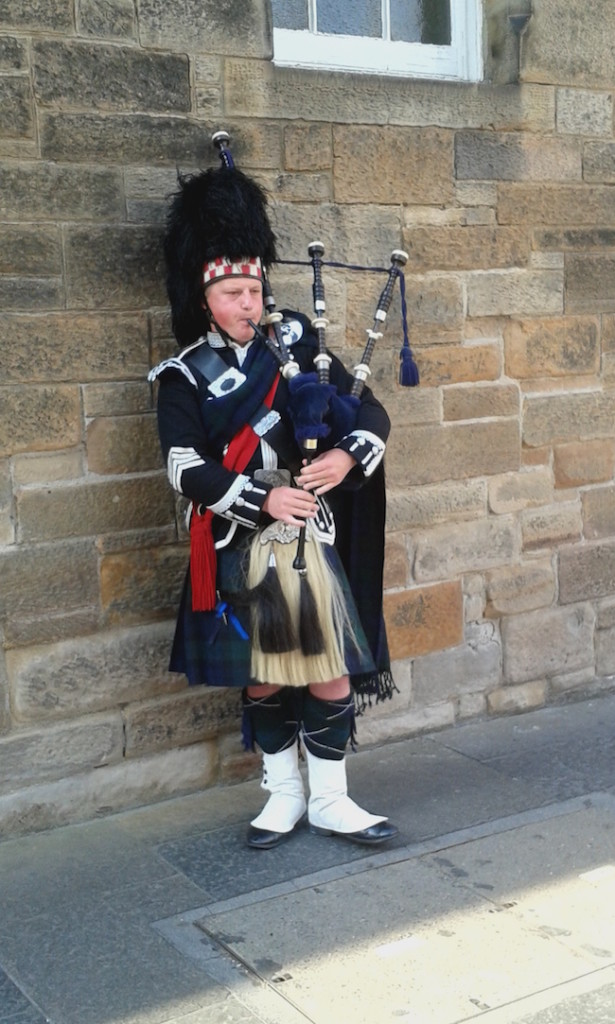A bagpiper in traditional clothing outside the Edinburgh Castle entrance