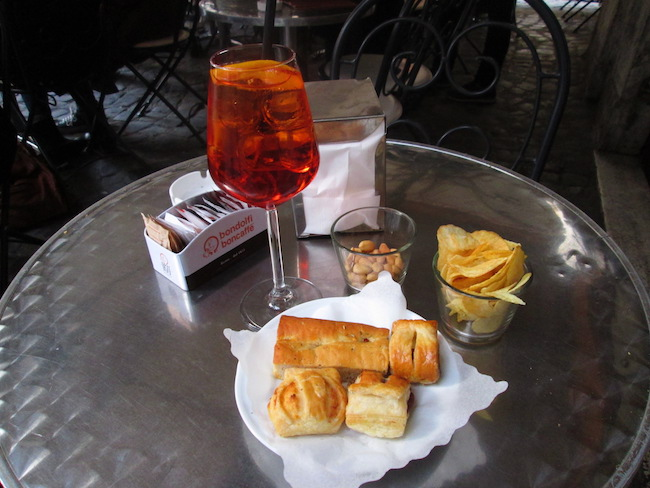 Enjoying an aperitivo with an aperol spritz at a sidewalk cafe