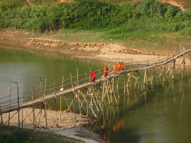 Monks crossing the river on a bamboo bridge