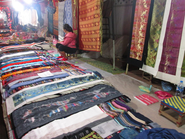 The night market is filled with vendors selling scarves and textiles